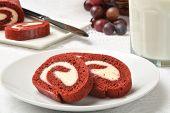pic of red velvet cake  - Sliced red velvet cake roll with a glass of milk - JPG