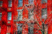stock photo of tenement  - Original red painted facade of a New York apartment building - JPG