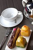 stock photo of collate  - Cakes a cup on the table in a tea room - JPG