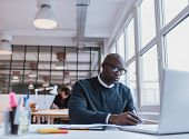 picture of bald man  - African man writing notes while working on a laptop in an modern office - JPG