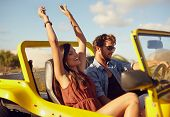 foto of road trip  - Cheerful young couple driving in a car. Enjoying road trip. Young man driving car with woman enjoying the ride with her hands raised.