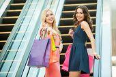 stock photo of escalator  - Two beautiful young women taking escalator in shopping mall - JPG