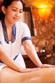 stock photo of thai massage  - Confident Thai massage therapist massaging female back and smiling - JPG