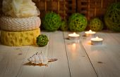 Постер, плакат: Sea shell on foreground sponges candles and rattan balls behind