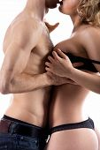 picture of love making  - Unrecognizable young half naked couple love play guy in jeans undressing girl taking off her black bra studio shot white background close - JPG