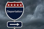 stock photo of deportation  - Deportation this way sign Blue Red and White highway sign with words Deportation with stormy sky background - JPG