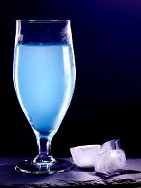 stock photo of cocktail menu  - Blue curacao drink with group cube ice on black background - JPG
