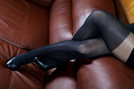 foto of stocking-foot  - Female feet in black stockings on a leather sofa - JPG