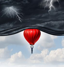 image of emotion  - Positive outlook and recovery concept as a person or businessman riding a red hot air balloon lifting the dangerous dark stormy skies to reveal a bright warm blue sky as a mindset symbol of managing economic or emotional perception - JPG