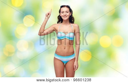 people, fashion, swimwear, summer and beach concept - happy young woman in bikini swimsuit pointing finger up to something imaginary over green holidays lights background