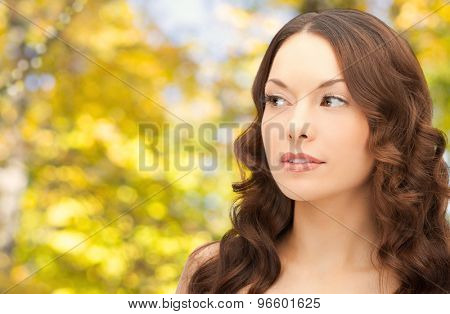 beauty, people and health concept - beautiful young woman with bare shoulders over yellow autumn background