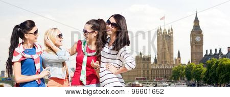 summer, holidays, vacation, friendship and people concept - happy teenage girls or young women in sunglasses talking and laughing over houses of parliament in london background