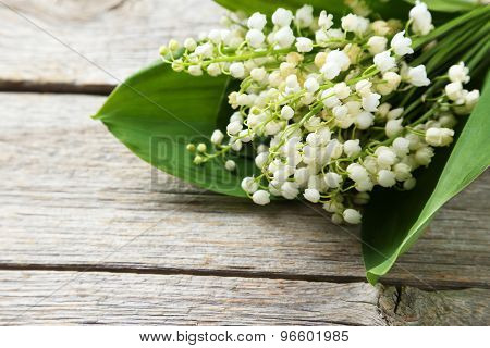 Lily Of The Valley With Leaves On Grey Wooden Background