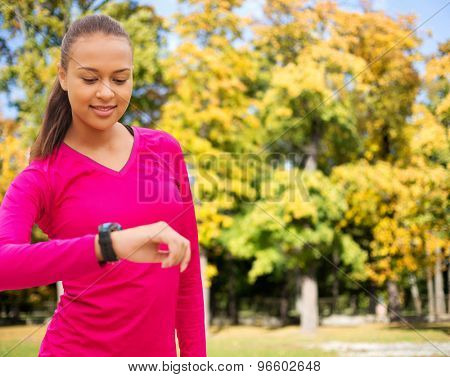 sport, fitness, technology, healthcare and people concept - smiling young african american woman with heart rate watch over autumn park background