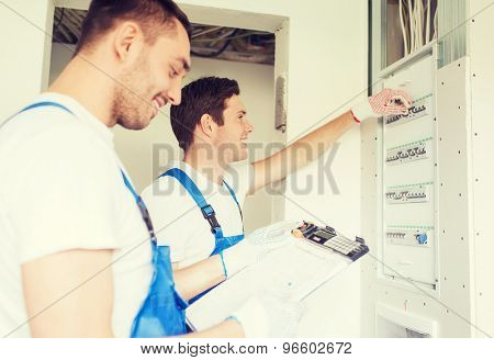 business, building, teamwork and people concept - group of smiling builders with clipboard and electrical panel indoors