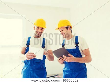 building, renovation, technology, electricity and people concept - two builders with tablet pc computers indoors