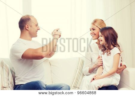 family, child, photography and home concept - smiling happy father taking picture of mother and daughter