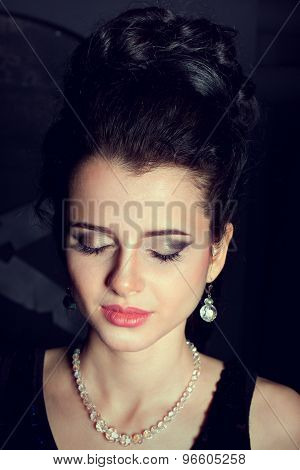 Portrait of young model with big lips and make up, brunette, black background Fashion look