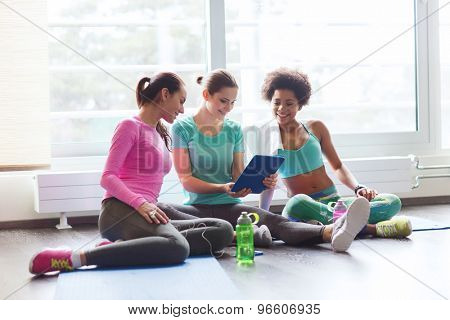 fitness, sport, friendship, technology and lifestyle concept - group of happy women with tablet pc computer in gym