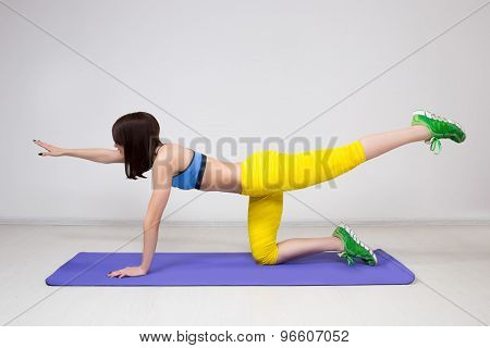 happy cutie athletic girl ,  execute exercise on muscles belly  and smile