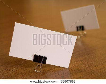 Business cards with paperclip fastener on a desk.