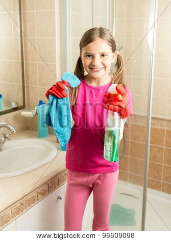 Cute Girl Doing Cleaning At Bathroom Holding Rag And Spray