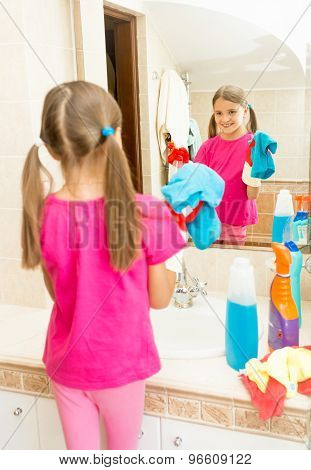 Little Girl Polishing Mirror At Bathroom With Cleanser