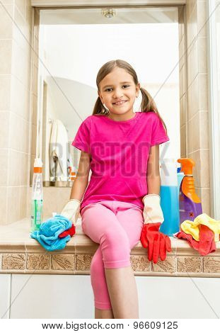 Smiling Girl Sitting On Sink At Bathroom While Doing Cleaning