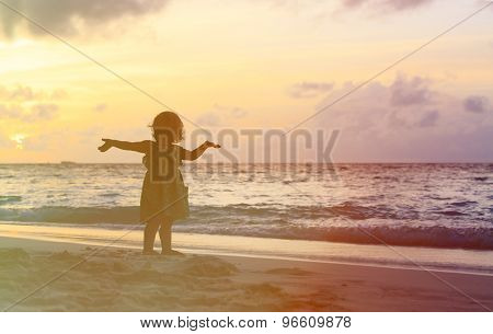 Silhouette of happy little girl with hands up to the sky