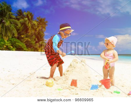 little boy and toddler girl building sandcastle on beach