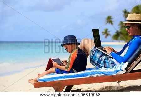 family with laptop and touch pad on beach