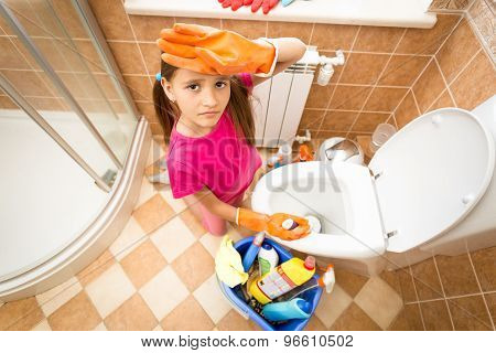 Portrait Of Upset Tired Girl Cleaning Toilet With Brush