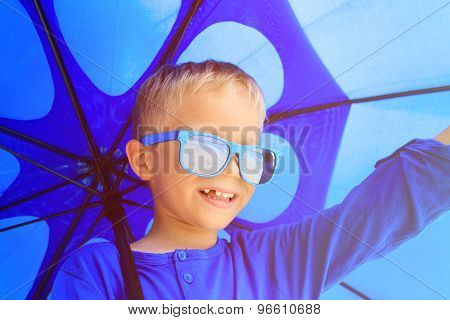 Selfie of little boy with umbrella on rainy summer day