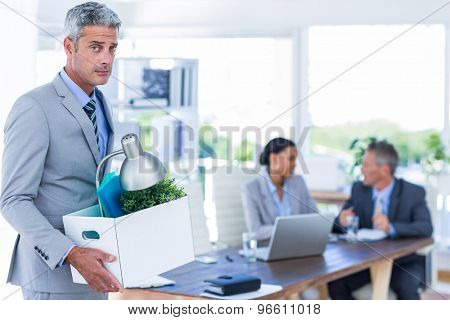 Businessman holding box with his colleagues behind him in office