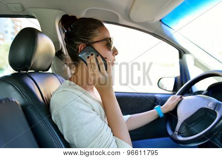 Woman driving and talking by cellular phone