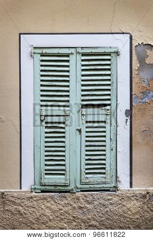 Old french windows with blue closed shutters in Villefranche-sur-Mer, France.