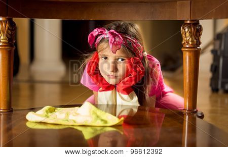 Portrait Of Tired Sad Girl Cleaning Wooden Table