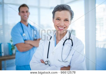 Portrait of two smiling colleagues doctors with arms crossed