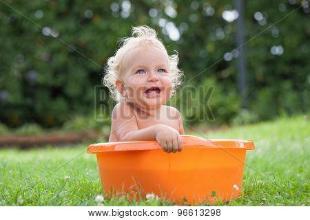 Cheerful Happy Cute Curly Baby Is Bathed In Orange Pelvis