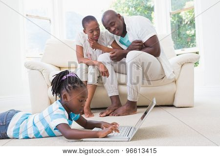 Pretty couple sitting on couch and their daughter using laptop in living room