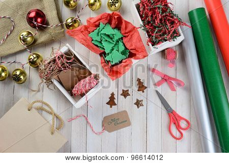 Overhead view of Christmas wrapping supplies on a rustic wood table. Scissors, ribbon, bells, tags, paper rolls, gift bag, string, ornaments and crepe paper are displayed.