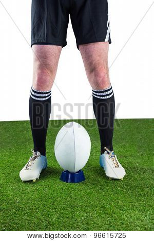 Low angle view of a rugby player ready to make a drop kick