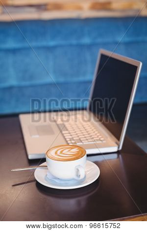 Close-up of laptop and coffee on table in the coffee shop