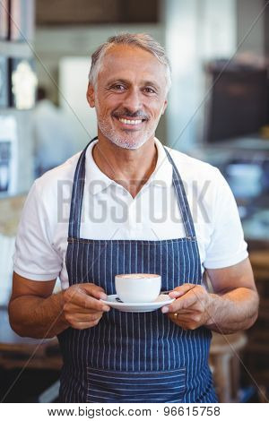 waiter smiling and holding cup of coffee at the cafe