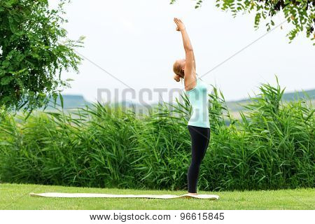 Lady Is Practicing Half Moon Yoga Pose In The Nature