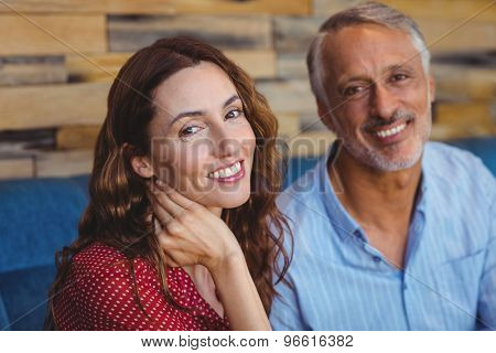 Cute couple smiling at the camera at the cafe