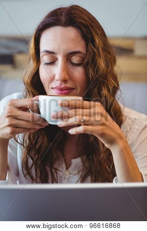 Businesswoman having coffee while working on laptop