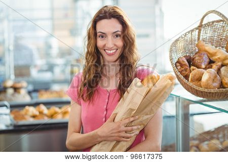 Smiling young brunette with baguettes at the bakery
