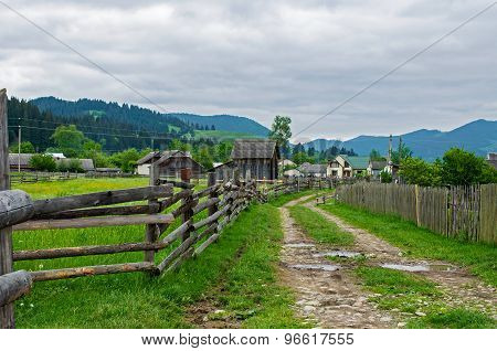 Rural landscape with a dirt road leader in mountains