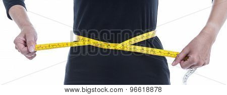 Weight Loss Concept, The Woman In Black Tries To Reduce Her Waist By Yellow Measuring Tape On White
